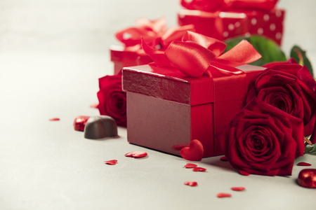 Foto de Valentine's Day concept. Gift with red bow on the wooden background Valentines gift box tied with a red satin ribbon bow on rustic background.  - Imagen libre de derechos