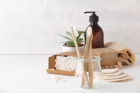 Photo pour Zero waste, Recycling, Sustainable lifestyle concept. Eco-friendly bathroom accessories: toothbrushes, reusable cotton make up removal pads, make up remover in a glass container, natural brushes, handmade soap, bamboo ear sticks - image libre de droit