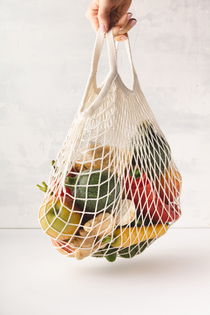 Photo pour Woman's hand holding a cotton bag of mixed fruit and vegetables. Zero waste, Recycling, Sustainable lifestyle concept - image libre de droit