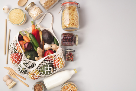 Photo pour Zero waste concept. Eco bags with fruits and vegetables, glass jars with beans, lentils, pasta. Eco-friendly shopping, flat lay - image libre de droit