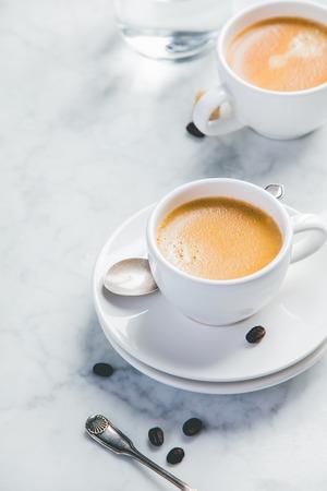 Foto de Coffee composition on white marble background. Coffee espresso in white cups - Imagen libre de derechos