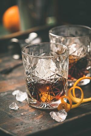 Foto de Alcoholic cocktail  with orange peel and ice on wooden table - Imagen libre de derechos