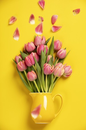 Photo pour This feminine, floral stock photograph features pretty Fresh pink tulips in a jug on yellow background. Easily downloaded, this stock photo is perfect to use with your website, social media digital marketing. - image libre de droit