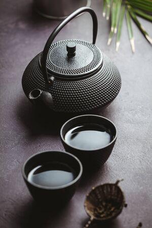 Photo pour Traditional Asian tea ceremony arrangement. Iron teapot, cups, dried green tea leaves, ginger and tropical leaves over purple concrete background, top view, copy space - image libre de droit