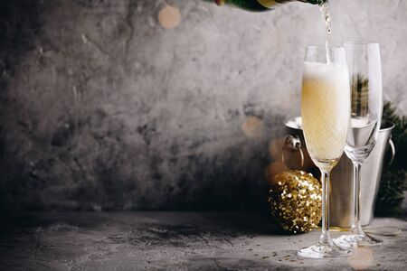 Photo for Champagne pouring into glasses and Christmas decorations - Royalty Free Image