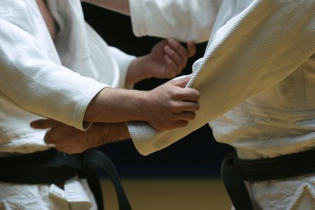 Judo fighters sparring off in a battle of body and mind - selective focus and visible grain