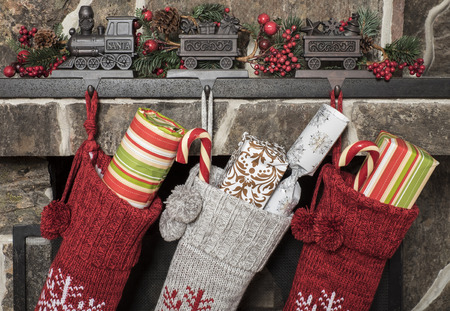 Photo for Stuffed stockings hanging on a fireplace on christmas morning - Royalty Free Image