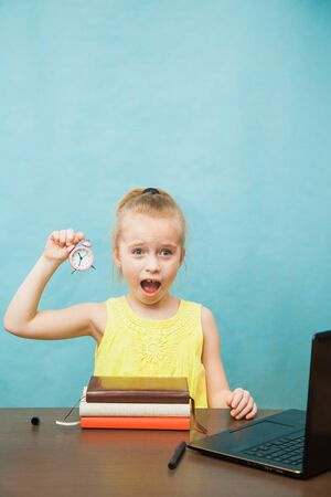Photo for Little elementary age girl homeschooling with books, laptop and alarm clock. Over worked pupil do lessons at home. Time management on qaurantine, self-isolation and social distancing concept. - Royalty Free Image