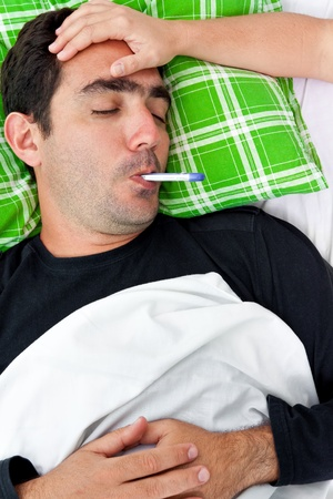 Portrait of a sick hispanic man laying in bed with a thermometer in his mouth while a doctor