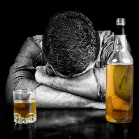 Foto de Black and white image of a drunk man sleeping with his head on a table and a bottle of whisky   the bottle and glass have color  - Imagen libre de derechos