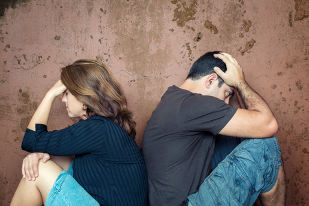 Foto de Divorce,fight,problems - Young couple angry at each other sitting back to back - Imagen libre de derechos
