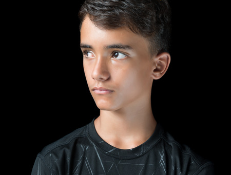 Photo pour Portrait of a serious hispanic teenage boy isolated on black - image libre de droit