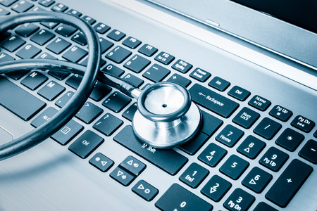Foto de Computer system health or auditing - Stethoscope over a computer keyboard toned in blue - Imagen libre de derechos