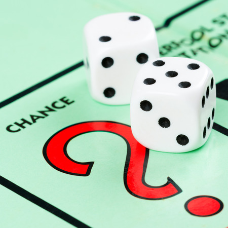 Photo pour Pair of dice next to the CHANCE card drawing space in a Monopoly game board - image libre de droit