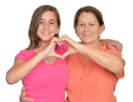 Foto de Hispanic teenage girl and her grandmother hugging and doing a heart sign with their hands - Imagen libre de derechos