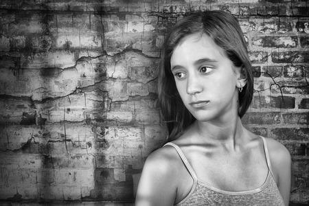 Foto de Sad and lonely teenage girl standing next to a grunge brick wall - Imagen libre de derechos