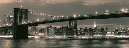 Photo for Vintage image of the Brooklyn Bridge illuminated at night with reflections on the East River - Royalty Free Image