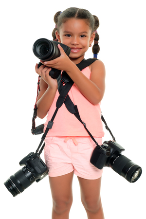 Photo pour Cute multiracial small girl carrying three professional cameras - Isolated on a white background - image libre de droit