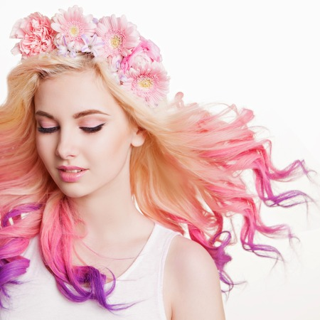 Photo pour Youth women with curly colored hair and flowers. white and pink background. Beauty. Flying Hairs - image libre de droit