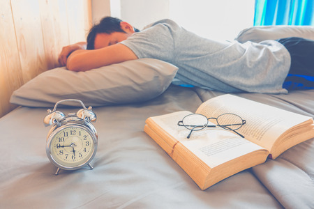 Photo pour A man sleeping on bed after read book - image libre de droit