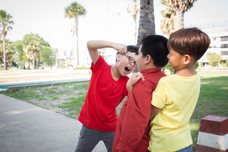 Photo for Young boy students fighting  in the park - Royalty Free Image