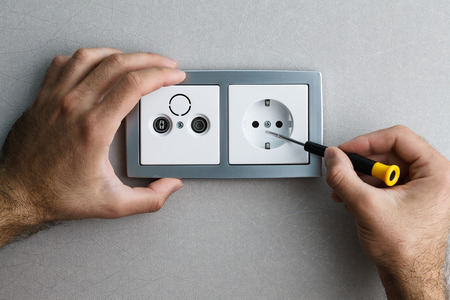 Foto de Installing a silver wall-mounted AC power socket with a screwdriver on a grey wall, renovating home. Close up view. - Imagen libre de derechos