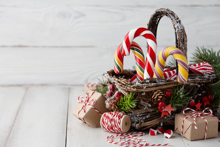 Photo pour Christmas wicker basket with striped candy canes and gifts on white wooden table, festive decoration - image libre de droit