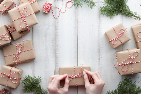 Photo pour Wrapping presents and gift boxes in kraft paper with fir tree decorations on white wooden background, copy space - image libre de droit