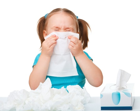 Little girl blows her nose, isolated over white
