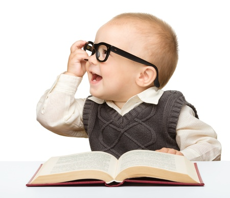 Photo for Cute little child play with book and glasses while sitting at table, isolated over white - Royalty Free Image