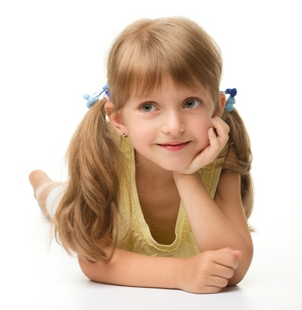 Portrait of a cute happy little girl laying on floor, isolated over white