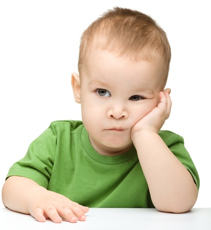 Portrait of a cute and pensive little boy support his head with hand, isolated over white