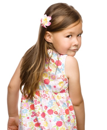 Little girl is looking back over her shoulder, isolated on white