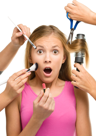 Photo pour Makeover process of a young teen girl, few hands are helping to apply makeup and cut hair, isolated over white - image libre de droit