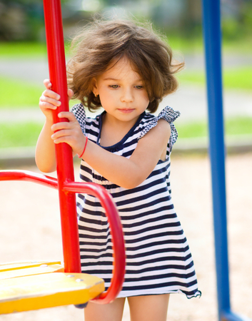 Young girl is playing in playground, outdoor shoot