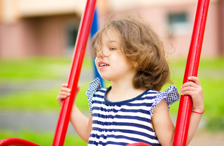 Young happy girl is swinging in playground, outdoor shoot