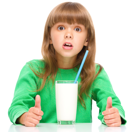 Photo for Cute little girl drinks milk using a drinking straw, isolated over white - Royalty Free Image