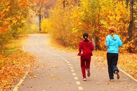Two young girls run in the park.