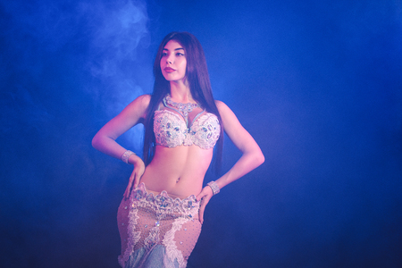 Photo for Woman in exotic costume sexually moves semi-nude body. Sexy traditional oriental belly dancer girl dancing on blue neon wall. Muslims, temptation concept. Spectacular show - Royalty Free Image