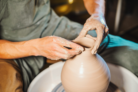 Photo pour Unknown craftsman creates jug. Focus on hands only. Small business, talent, inspiration concept. Overhead view. Working process of mans work at potters wheel in art studio - image libre de droit