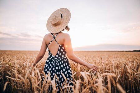 Photo for Unrecognizable woman in retro style dress and hat posing in wheat golden field. Travel, harvest, nature, old fashion concept. - Royalty Free Image