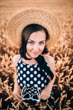 Photo for Portrait of woman in retro style dress and hat posing in wheat golden field. Travel, harvest, nature, old fashion concept. - Royalty Free Image