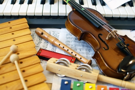 Photo for Musical instruments for children: xylophone, children's violin, tambourine, flute, harmonica, piano keyboard.  - Royalty Free Image