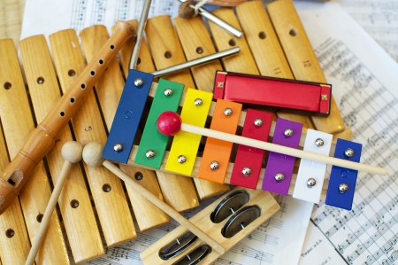 Photo for Some typical, colorful music instruments as used mostly by children. The musical score in the background is in the Public Domain.  - Royalty Free Image