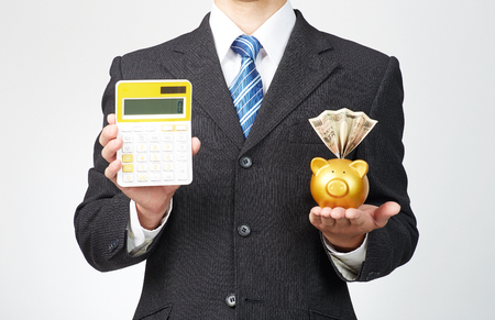 businessman holds tablet with money box and calculator