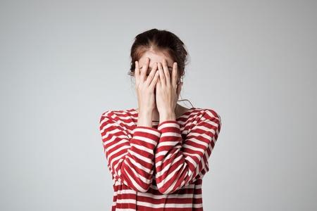 Foto de Pretty caucasian girl covers her face with her hands - Imagen libre de derechos