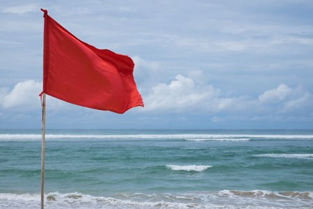 Foto de A red warning flag on the beach in the Nuca Dua Bali, Indonesia. Danger to swim in ocean - Imagen libre de derechos