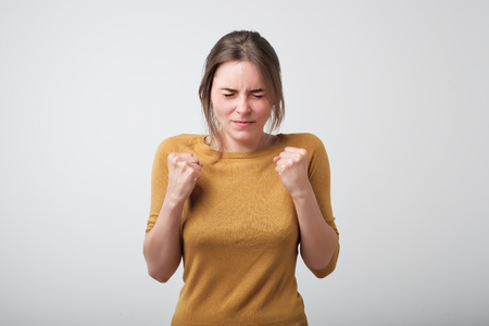 Photo for Young caucasian woman wishing for good luck. She is holding her fist and closing her eyes - Royalty Free Image