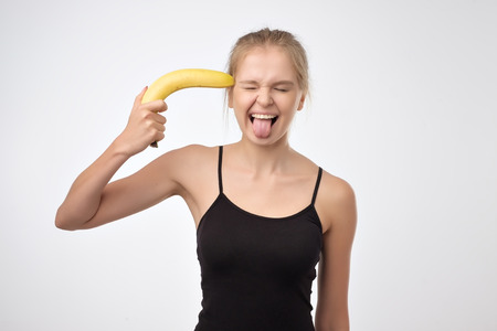 Photo pour A creative portrait of a beautiful blonde girl holding banana like a gun near head - image libre de droit