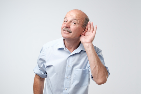 Photo pour Portrait of senior casual man which overhears conversation over white background. Speak loudly please concept. What did you say - image libre de droit